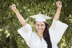 Raza mixta de graduación feliz adolescente en casquillo y vestido Foto de archivo