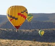 Razas del aire caliente de un trío del globo cerca de Sedona, Arizona Foto de archivo