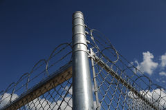 Razor and Barb Wire on top of Chain Link fence Stock Images