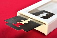 Razor blade and a white pvc box. One razor blade and a white pvc box Royalty Free Stock Image