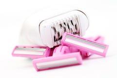 Razor and epilator. Pink razor and epilator on white - beauty treatment /focus on epilator Royalty Free Stock Photos