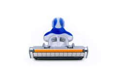 Razor from a Front View. A blue, silver and orange razor on a white surface and background Royalty Free Stock Photography