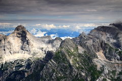 Razor and Pihavec peaks under layer of clouds, Julian Alps. Peaks of the Julian Alps Triglav National Park from Kanjavec: Razor left, Pihavec, Bovski Gamsovec Royalty Free Stock Photo