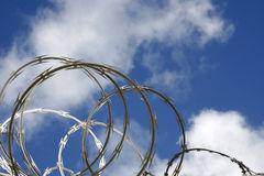 Razor wire. Against a blue sky with clouds stock photos