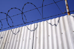 Razor wire and aluminum fence. Razor wire, barbed wire, and an aluminum fence. Picture taken near Long Beach, CA Stock Image