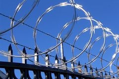 Razor wire and barbed wire. Razor or spiked wire and barbed wire on top of a spiked iron fence against a blue sky Royalty Free Stock Photos
