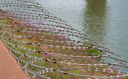 RAZOR WIRE BARRIER. Dam access secured by barbed wire barrier stock photography