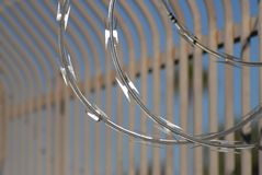 Razor wire closeup with bar fence Secrity Location. Security Fence with bars and razor wire sharp color blue sky blurred bars Stock Image