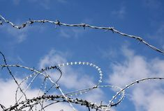 Razor wire clouds. Image of a blue sky day behind razor wire and barbed wire stock photography