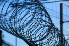 Razor wire. Fence with barbed/razor wire in front of blue sky. Shallow focus Stock Photos