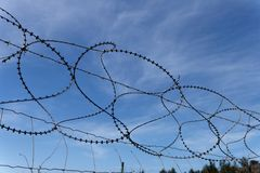 Razor wire fence over sky Stock Photography