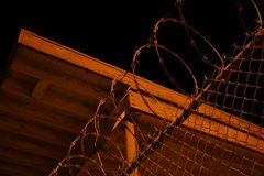 Razor Wire At Night. An eerie photograph of razor wire on top of a fence at a minimum security facility at night Royalty Free Stock Photography