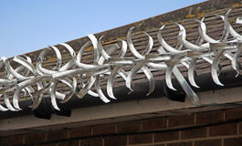 Razor wire security. Photo of razor wire fitted along guttering of roof to deter intruders etc Stock Photos