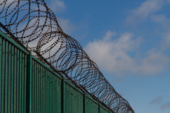 Razor wire on top of green fence guarding French ferry terminal. Stock Photos
