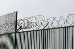 Razor wire on top of green fence guarding French ferry terminal. Royalty Free Stock Images