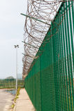 Razor wire on top of green fence guarding French ferry terminal. Stock Images