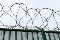 Razor wire on top of green fence guarding French ferry terminal. Royalty Free Stock Image