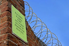 Razor wire and warning sign Royalty Free Stock Photography