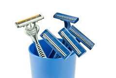 Razors in blue cup. Five razors in a blue glass isolated on white background Royalty Free Stock Images