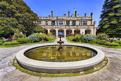 RBG Government House Fount. Colourful sunny summer day in Royal Botanic garden of Sydney with fountain and view on historic colonial palace in capital of NSW Royalty Free Stock Photography