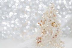 ?rbol de navidad blanco con las perlas y las gotas en la nieve al lado del fondo borroso hermoso del bokeh y de la guirnalda que  fotografía de archivo