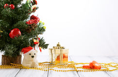 Árbol de navidad, caja de regalo del oro, bolas, oso del juguete, caramelos y decoraciones en la tabla blanca del vintage retro a Imágenes de archivo libres de regalías