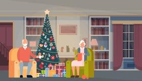 Árbol grande del verde de la Navidad de la familia con la bandera de la Feliz Año Nuevo de la decoración interior de la casa de l Fotografía de archivo libre de regalías