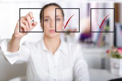 Business woman checking mark on checklist. Rbusiness woman checking mark on checklist with a red marker Stock Photos