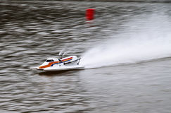 RC boat speeding on a lake. Remote controlled boat create splashes of water as it speed across a lake Stock Photos