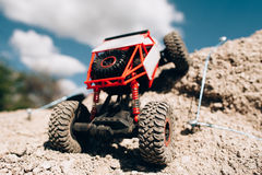 Rc car overcoming rock hill close-up. Crawler rising on rough surface of rocky rally track. Competitions radio-controlled toys concept Stock Image