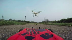 RC cars with a camera rides on the dirt road and filmed the quadrocopter, flying in front of the car stock footage