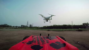 RC cars with a camera rides on the field and filmed the quadrocopter, flying in front of the car stock footage