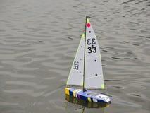 RC Model Sailboat on Lake. Radio Controlled Micro Magic Sailboat on Lake Royalty Free Stock Image