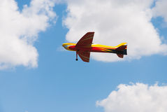 RC model yellow plane flying. Over blue sky with clouds Stock Photos