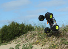 RC Nitro monster truck action. Action shots of a 1/8 scale radio control nitro powered monster truck on the beach and dunes Royalty Free Stock Photo
