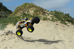 RC Nitro monster truck action. Action shots of a 1/8 scale radio control nitro powered monster truck on the beach and dunes Royalty Free Stock Photos