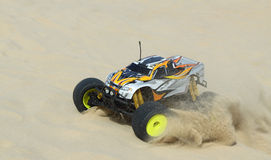 RC Nitro monster truck action. Action shots of a 1/8 scale radio control nitro powered monster truck on the beach and dunes Stock Photo