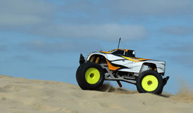 RC Nitro monster truck action. Action shots of a 1/8 scale radio control nitro powered monster truck on the beach and dunes Stock Image