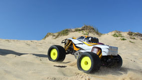 RC Nitro monster truck action. Action shots of a 1/8 scale radio control nitro powered monster truck on the beach and dunes Royalty Free Stock Photography