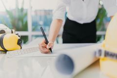 Rchitect hand drawing blueprint on working table Royalty Free Stock Image