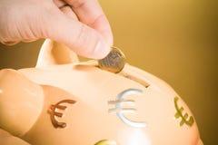 Räcka att sätta in ett mynt in i en spargris, begreppet för affär och spara pengar Royaltyfri Bild