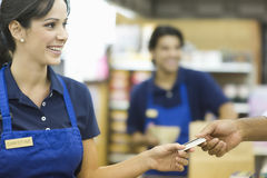 Räcka lojalitetkortet i supermarket Arkivfoto