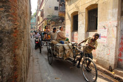 Rckshaw puller carrying goods on the road of Kolkata Stock Photo