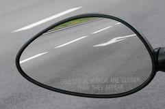 Rückspiegel mit warnenden Textgegenständen im Spiegel sind genauer, als sie erscheinen und Straße, seitliche Makronahaufnahme der Stockbild