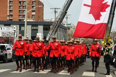 RCMP officers march in unison. Victoria BC,Canada,April 19th 2018.RCMP police officers in their red tunics march to the church for a funeral for a fallen officer Stock Photos