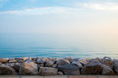 Peaceful quiet rock pier at sunrise with calm blue sea waves. A rcoky pier stands in front of calm see with a sense of peace stock image