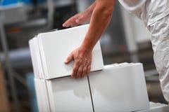 Ręczny pracownik przy linią produkcyjną rozdaje z pudełkami Zdjęcie Royalty Free