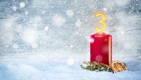 3rd Advent candle with snow. Christmas candle with a flame in shape of the number 3. Decorative background with snowflakes, cinnamon and a dried orange slice Stock Photo