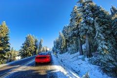 Röd bil på den snöig och iskalla vintervägen Arkivbild