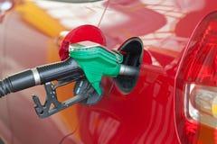 Röd bil som fylls med bränsle Royaltyfri Bild